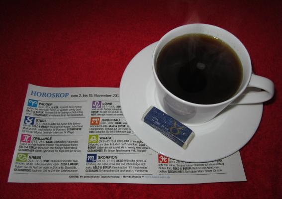 Kaffeetasse mit Sternzeichenzückerwürfel und Zeitungshoroskop